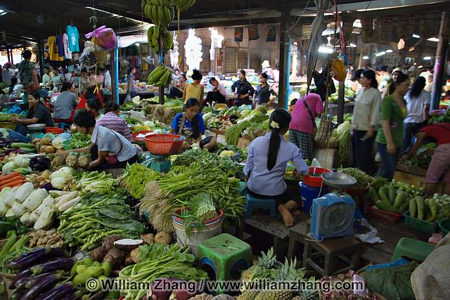 Seated vendors surrounded by vegetables. Siem Reap