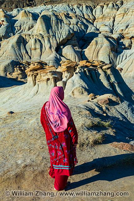 Woman gazing out over the hoodoos near Drumheller, Alberta