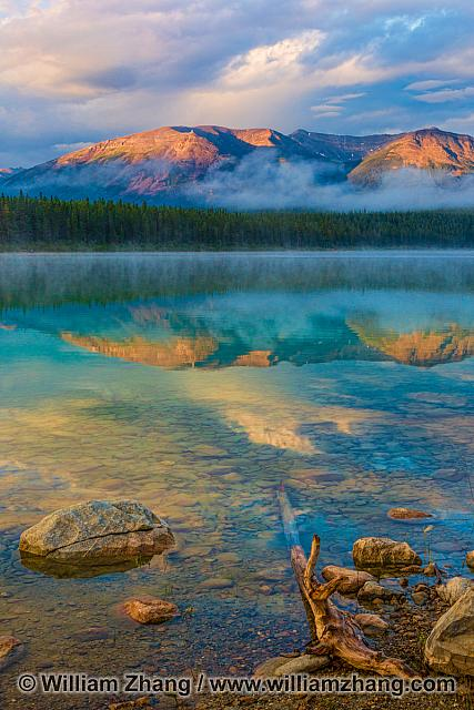 Mountain reflection in clear water of Patricia Lake at sunrise