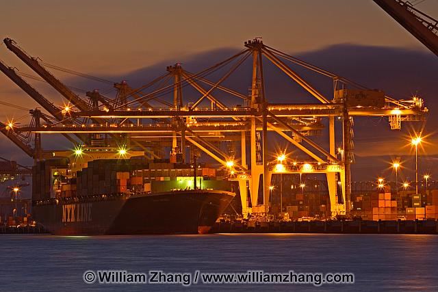 Cranes at night unload container ship at port. Oakland, CA