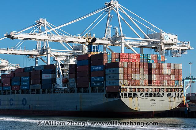 Cranes, shipping containers and freighter at port. Oakland, CA