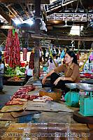 Woman sits behind meat counter at market. Siem Reap