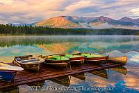 Calm water at Patricia Lake reflects mountains and sunrise