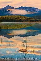 Clouds, mountains and trees reflected at sunrise in Patricia Lak
