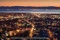 Lights of Oakland at night stretch to the bay. Oakland, CA