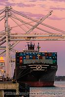 Freighter, cranes, and shipping containers at port. Oakland, CA