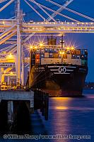 Container ship and lighted cranes at night at port. Oakland, CA
