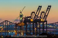 Twilight on port cranes and sections of Bay Bridge. Oakland, CA