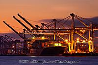 Container cranes and ship at night at port. Oakland, CA