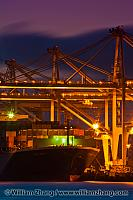 Container cranes at night above ship at port. Oakland, CA
