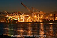 Bright lights from cranes on harbor waters at port. Oakland, CA